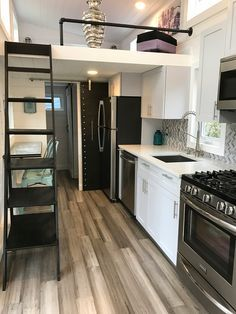 The kitchen is equipped with a full size range, overhead microwave, dishwasher, and an apartment size refrigerator.