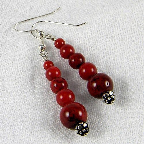 Looking for that perfect red for the upcoming holidays?  These graduated 5 bead red dyed natural coral earrings are the answer to this question.  The movement of the dangle enhances the gloss finish that adds a soft glisten to the neckline.  In contrast the silver plated findings bring a dramatic play of intense light.  The bottom of the earring dangle is an antiqued silver floral motif.  This motif is generic and can speak to any season of the year.  The beads are mostly a deep read but…