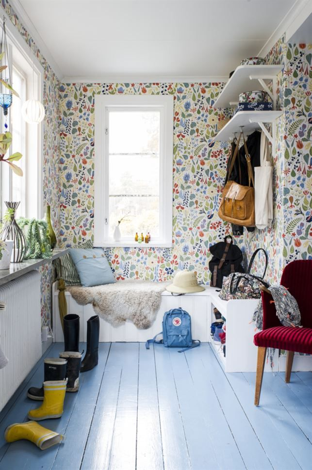 Blommig hall. Hallbänken har Björn byggt av överblivet material från golvet i köket. Även hatthyllorna är hemmasnickrade. Väggarna är klädda med tapeten Herbarium från Boråstapeter, och golvet är målat i en himmelsblå kulör från Tresjerner.