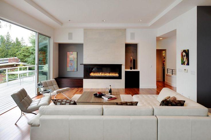 Salotto minimal moderno, con pochi oggetti ma di grande qualità. Pavimenti parquet in legno, divani in pelle bianca e camino chiuso