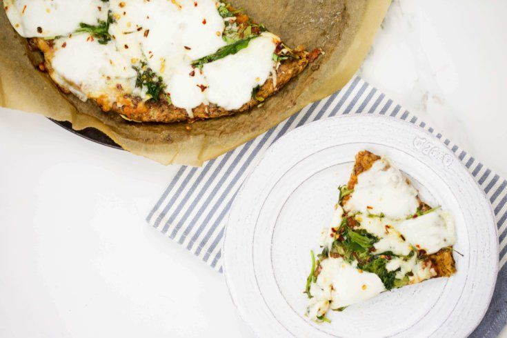 This Florentine pizza recipe combines a variety of tasty, high-quality cheeses with tomato sauce, spinach, eggs and spice on a low-carb zucchini crust.