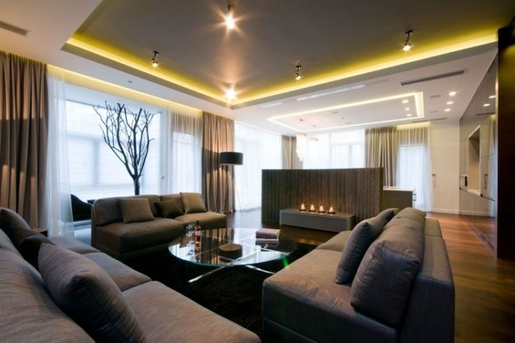 graue Wohnzimmermöbel und runder Glas Couchtisch