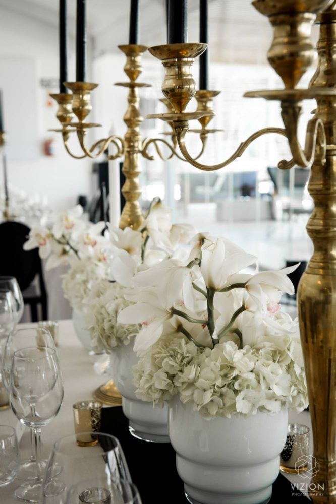 Elize & Stefan - Wedding Showcase | The Aleit Group  Black and gold wedding. Gold candle holder. White flowers. Wedding decor, White lilly. Table setting. Laurent Venue. Vizion Photography and Films. South Africa.