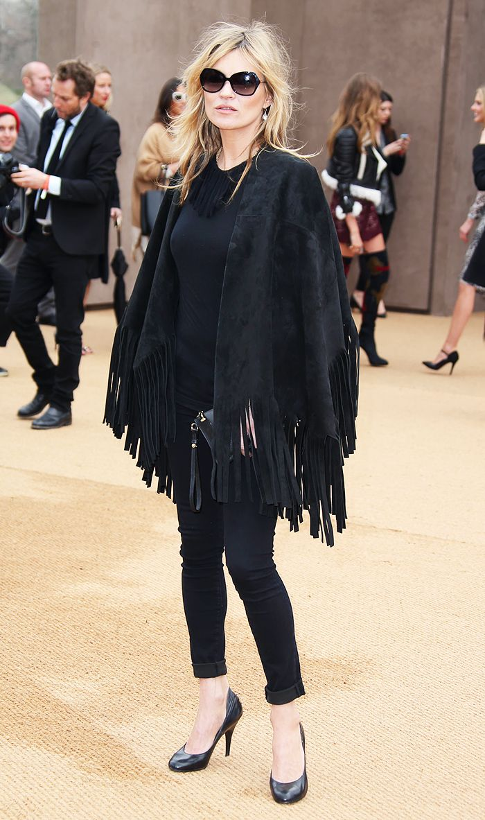 Kate Moss wearing black cuffed skinny jeans, and a black fringe cape at London Fashion Week