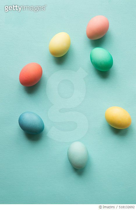 Scattered colorful Easter eggs on a plain aqua blue background shot from above - gettyimageskorea