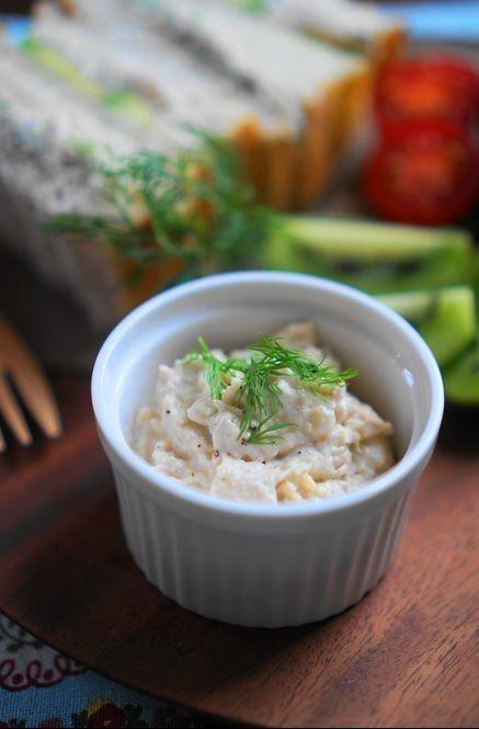 ツナと大豆のチーズディップ       バゲットやサンドイッチに使える、ヘルシーでお洒落なディップ    クリームチーズ入りでリッチな風味は、クセになる美味しさです   うさぎのシーマ     材料 (作り易い分量) ツナ水煮缶 (小) 1缶(70g)   水煮大豆 1/2袋(75g)   玉葱(みじん切り) 1/4個 (50g)   クリームチーズ 50g   ヨーグルト(プレーン) 小さじ2   レモン汁 小さじ1/2   白味噌 小さじ1/2   塩 小さじ1/4   砂糖(きび砂糖使用) 小さじ1/2   黒胡椒(お好みで) 少々   ディル あれば少々    作り方 1  玉葱はみじん切りにし、水にさらしてからしっかりと水気を切っておく    ツナは水気を切り、大豆は軽く湯通しする    2  フードプロセッサーに玉葱以外の材料を入れて滑らかに撹拌 ⇛ボウルに移し、①の玉葱を加え混ぜる    3  ブラックペッパーと塩(分量外)で好みに味を調え、ディルを添えて出来上がり☆    4  ライ麦パンでサンドイッチに☆…