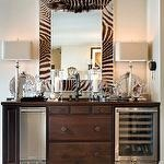 Clever repurpose of this dresser into a bar with ice maker ad wine frig. Love the zebra mirror