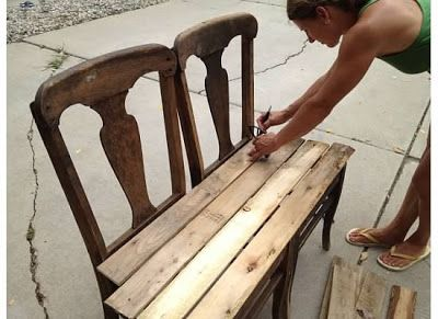Creating a bench out of two old chairs and a pallet. To make a weather resistant option use outdoor chairs that have lost their webbing, for example.
