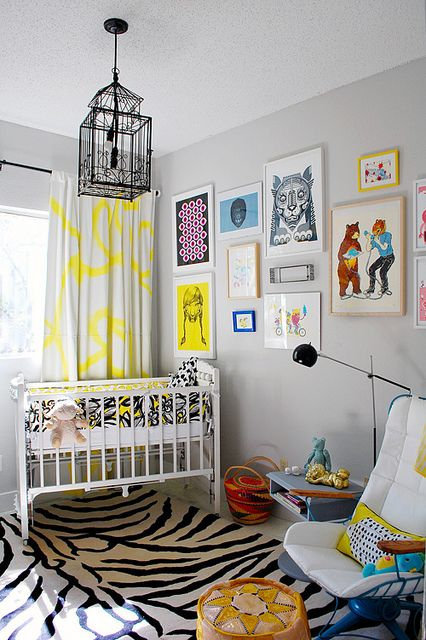 Gray is the new all-purpose neutral for a colorful, eclectic nursery filled with eye-popping patterns and a gallery of imaginative artwork. Love the birdcage repurposed as pendant lighting.