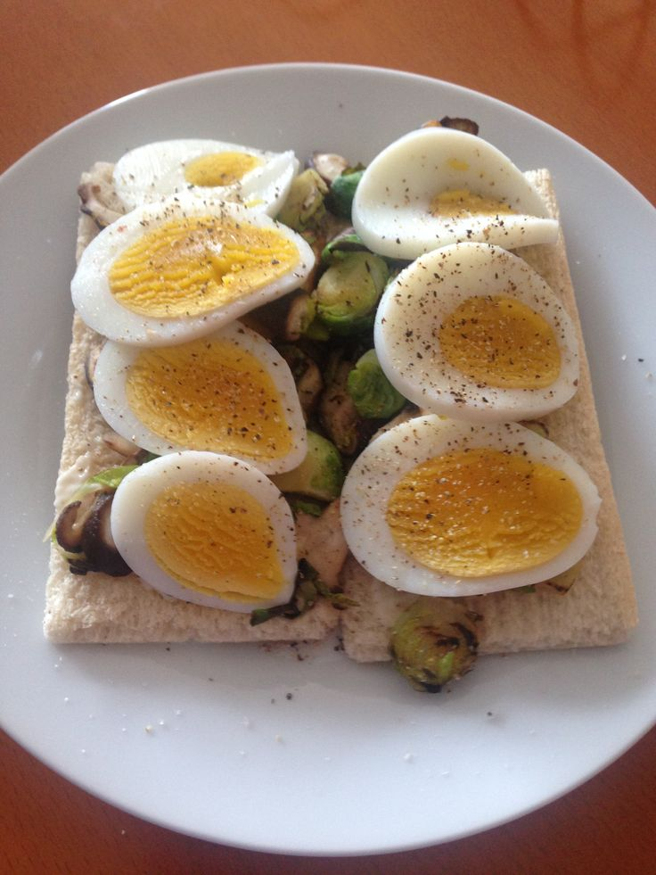 Pepper cracker bread, thin smear of light mayo, topped with stir fried chestnut mushroom and brussel sprouts, boiled egg seasoned with cracked pepper and salt