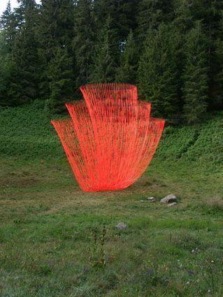 """Land art. Pier Fabre L'œuvre de Pier Fabre, """" le Réveil """", s'est implantée au centre du cratère du plus jeune volcan Français, le puy de Montchal. Cinq cent rubans de couleur rouge-orangé dansent dans le vent, qui donne vie à cette œuvre suspendue"""