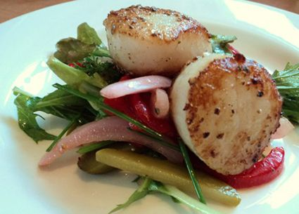Seared scallops on a bed of mixed greens and pickled vegetables