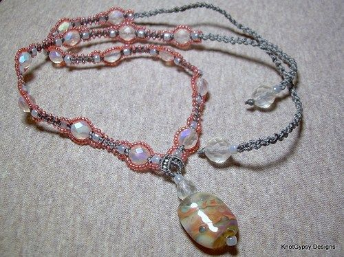 An original KnotGypsy design!  Hand knotted with bonded nylon bead cord in gray.  Beaded with tiny seed beads in iridescent peach, larger seed beeds in pearly gray, and faceted round glass focal beads