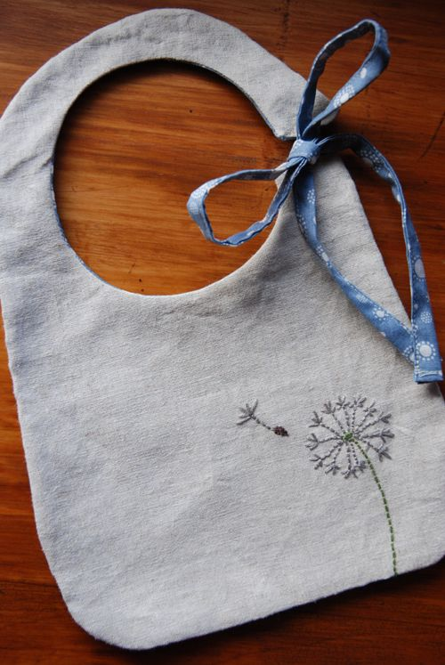 Beautiful linen baby bib with simple dandelion embroidery. Tied up all in a bow...