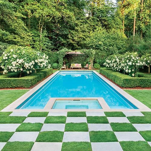 This backyard pool achieves a classic elegance through the use of a checkerboard paving scheme, a trellised wooden pergola and neat olive hedgerows. Image by Roger Foley via Southern Living.