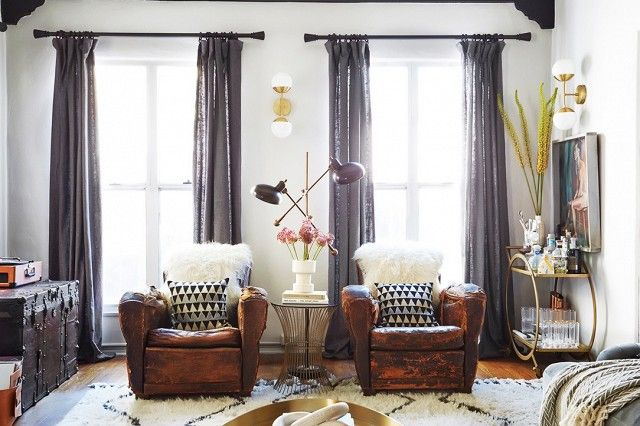 Eclectic living space with matching vintage leather armchairs, gray curtains, and a large rug