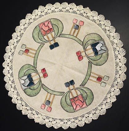 """Arts & Crafts round table mat, H. E. Verran Co. Inc. Royal Society, #591, ca.1911-1912, floral motif in red, black, gold and blue floss on oatmeal linen fabric with brown and green stenciling, satin and outline stitches, lace border, 24""""dia.  