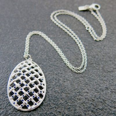Weave Large Hollow Egg Pendant in Silver scattered with Blue Sapphire gemstones.
