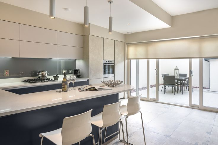 the scuffed concrete tile and a light grey granite slab in the garden allows a visual perception that the garden and kitchen are one room with dividing sliding doors.