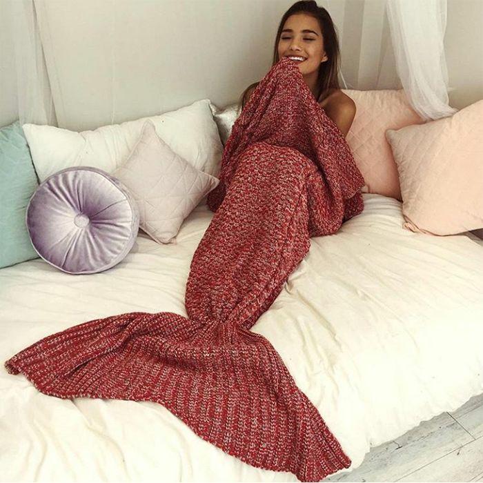 mujer en cama con cola de sirena tejida