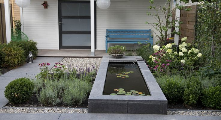 Rodenburg tuinen: moderne achtertuin bij een nieuwbouwwoning. Deze kleine achtertuin heeft elementen die de tuin toch bijzonder maken. De houten vlonder, het split en de oud hollandse tegels maken het tot een veelzijdige tuin. Daarbij is het waterelement een echte eye catcher in deze moderne en tegelijkertijd tijdloze tuin.
