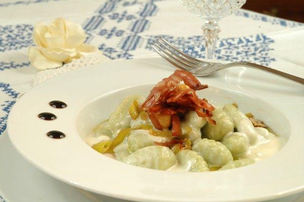 Gnocchi verdi alla fonduta di parmigiano con nocciole, porri e chips di mortadella