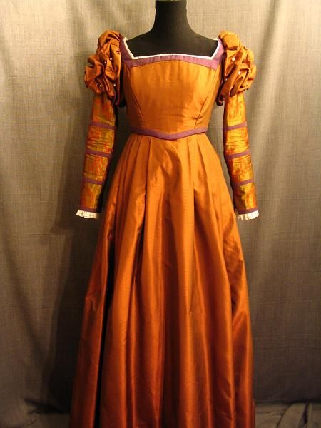 Abito in raso arancio in stile tudor con maniche a palloncino nella parte superiore. Costo £60