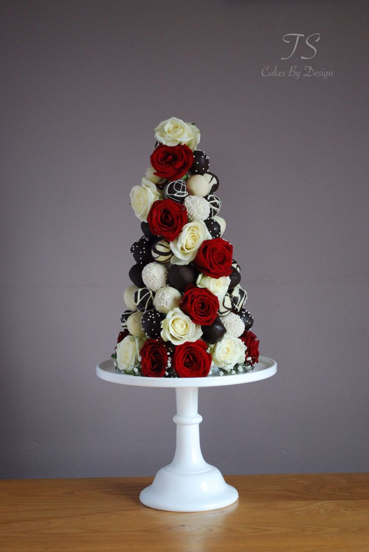 Chocolate strawberry tower - strawberries dipped in white & dark chocolate with red & white roses as decor.