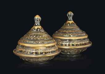 A PAIR OF GILT CLEAR GLASS COVERED BOWLS (SAHANS) OTTOMAN TURKEY, 19TH CENTURY Each on plain base with rounded body and straight rim, the gilt decoration with scrolling vines, the base with radiating leaf motifs, with spherical finials rising from the ribbed domed lids decorated with foliated garlands and scrolling tendrils, intact Each 9in. (22.8cm.) high, 9in. (22.8cm.) diam. (2)