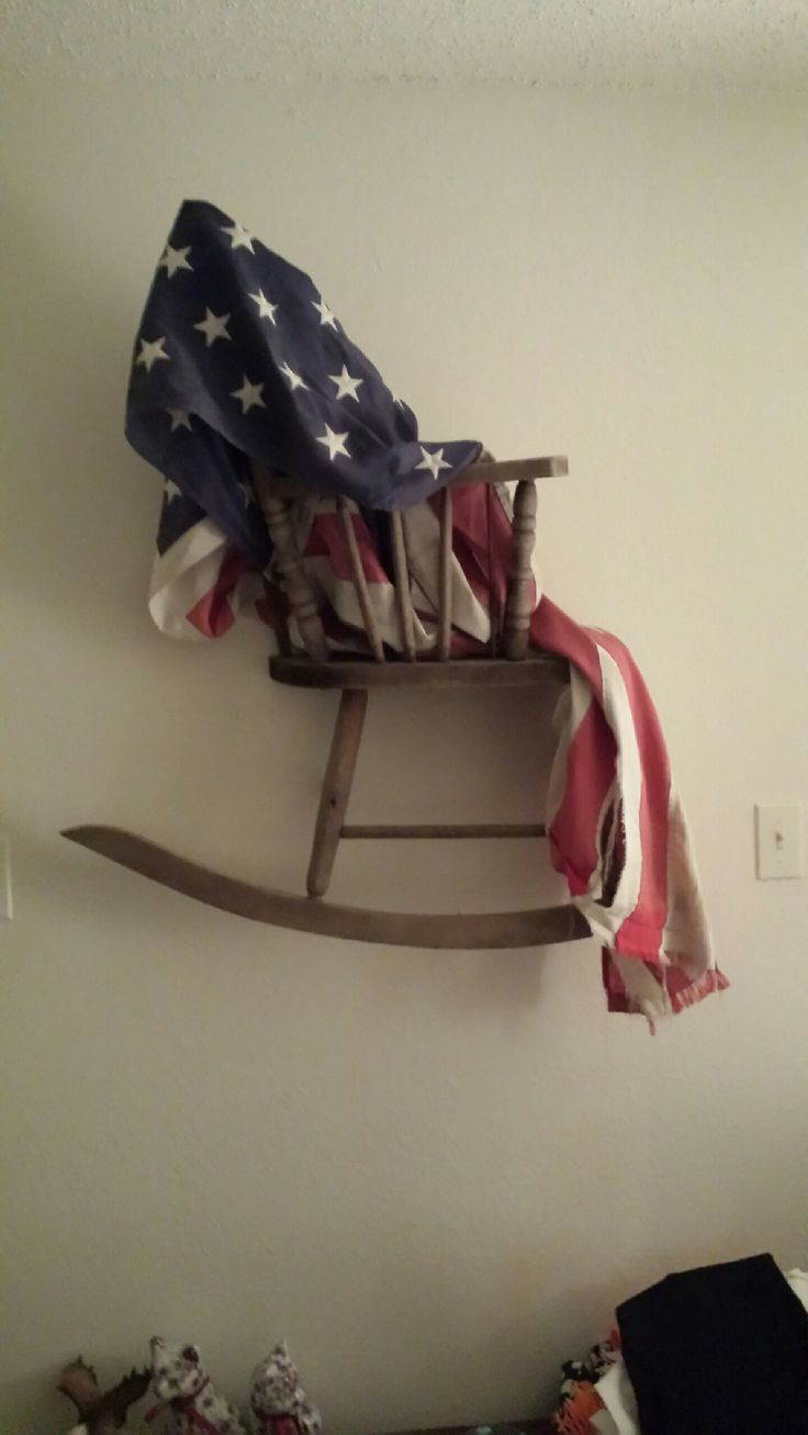 My brother made this by cutting an old rocking chair in half and attaching it to his wall. He then took a worn American Flag and draped it over the chair giving it a nice rustic appearance.