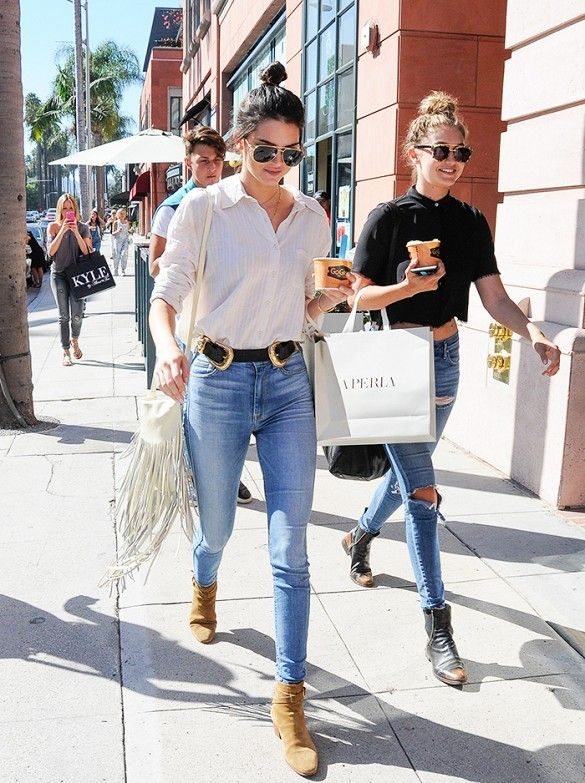 Kendall Jenner wears a white button-down shirt, belted skinny jeans, suede Saint Laurent boots, aviator sunglasses, and a white fringe shoulder bag: