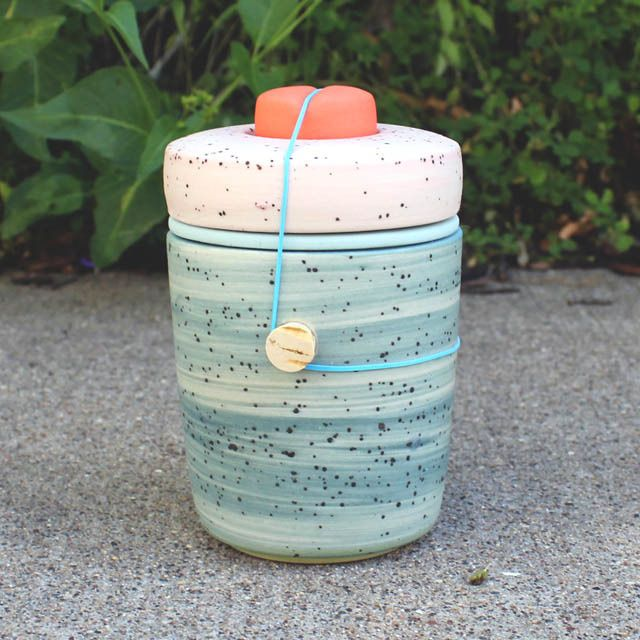 A beautiful, multicolor 4 part ceramic object in summery oranges and blues.  A fine vessel with countless applications.- Slip-cast porcelain - Cork stoppers at the sides- Rubber band closure
