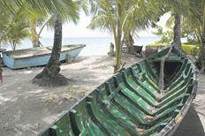 Colombia. La Isla de Providencia: Caribe en calma. Bajo la sombra de cocoteros, un bote de regatas típico del Caribe colombiano.