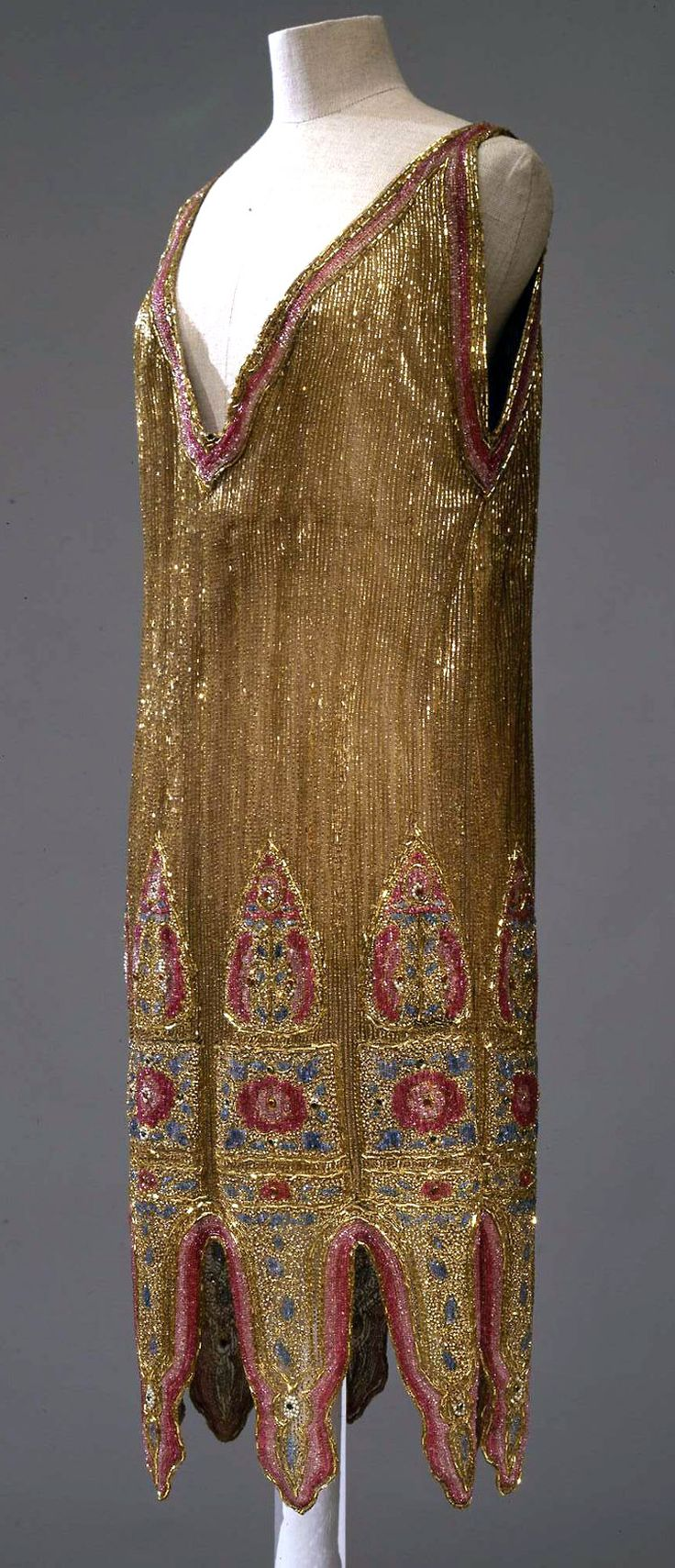 Evening dress, Italian manifacture, ca. 1925. Light brown slik tulle with deep V neckline, completely embroidered in gold coloured glass straws, strass in different colours and gold thread. Photo: Marcello Bertoni. Collection Galleria del Costume di Palazzo Pitti via Europeana Fashions