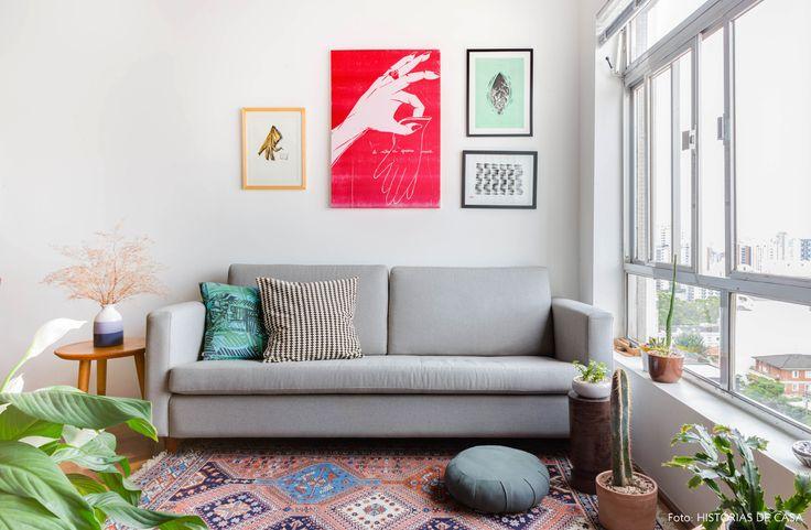 Sofá cinza, parede galeria com quadros, tapete étnico e muitas plantas na sala de estar desse apê.