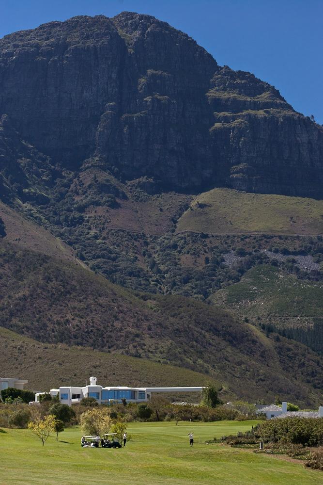 Golfers dwarfed by the majestic mountains.