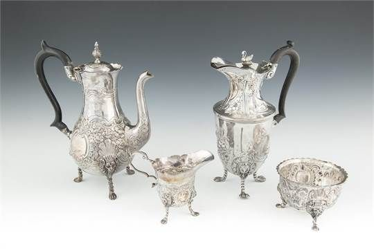 AN IRISH EDWARDIAN THREE PIECE SILVER COFFEE SERVICE, Dublin 1907, makers mark of West & Son, comprising coffee pot, creamer and sugar bowl, of baluster form, the bodies with decorated with repoussé, chased and engraved foliate panels, raised on lion mask and rope twist legs on paw feet; together with a matched hot water jug