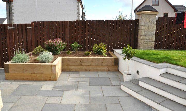 Fairstone black limestone paving and timber sleeper planters