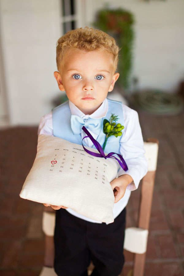 A ring bearer wearing a light blue vest and bow tie with a green boutonniere, white collared shirt and black pants. The ring bearer pillow includes a calendar print with a heart drawn around the wedding date along with purple ribbon.