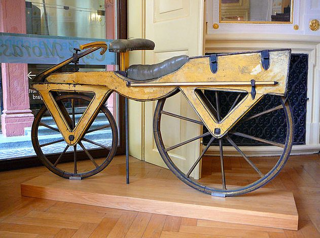 """Photo: a Laufmaschine, c. 1820, on display at the Kurpfälzisches Museum in Heidelberg, Germany. Credit: Gun Powder Ma; Wikimedia Commons. Read more on the GenealogyBank blog: """"The Tracena: America's First Bicycle"""" https://blog.genealogybank.com/the-tracena-americas-first-bicycle.html"""