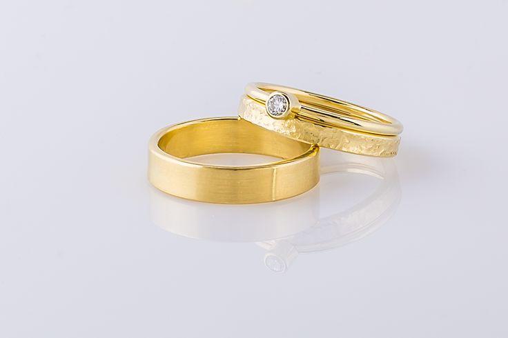 Trouwringenset waarbij de damesring uit twee losse ringen bestaat, eentje met een bewerking en de andere met een diamant. De herenring is mat afgewerkt.