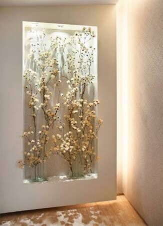 Parede de flores artificiais com recuo de gesso e iluminação