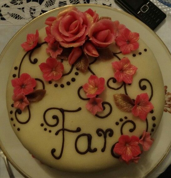"""Pink marzipan flowers with gold dust, chocolate scrolls. Says """"dad"""" in danish. Picture only."""