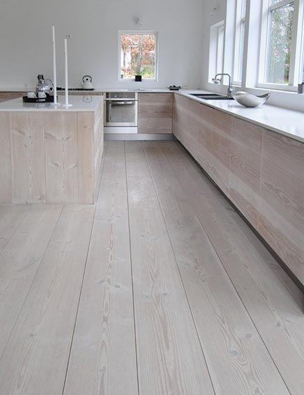 De massief houten vloer die gebruikt is in deze woning, is ook gebruikt om de deuren van de keukenkastjes te maken. Om precies te zijn gaat het om een massief spar, die de keuken een robuuste, moderne en levendige uitstraling geeft.