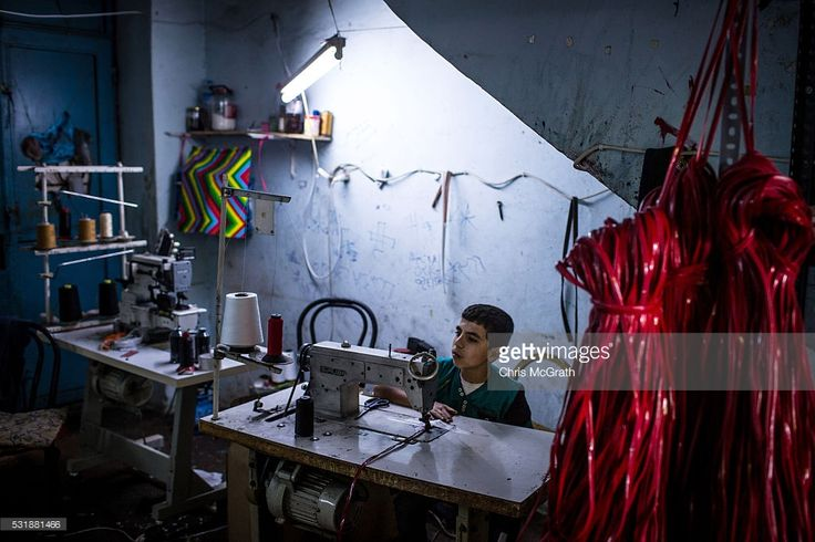 A Syrian refugee boy makes shoe parts at a Turkish owned shoe workshop on May 16, 2016 in Gaziantep, Turkey. Since fleeing the war and after the new E.U - Turkey deal effectively shutting down routes to Europe for many Syrian refugees, living in Turkey has become their only option, however there is very little stable work and little hope of building a future. Turkey's massive and largely unregulated garment industry is an attractive option for Syrians to work both legally and illegally…