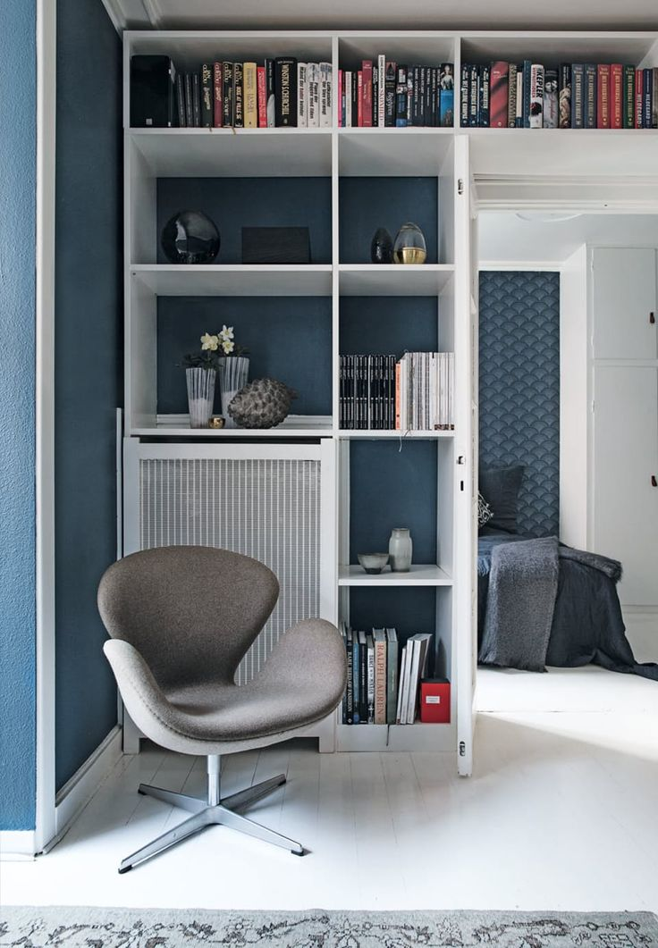 Amazing floor to ceiling bookshelf with shelves for ceramics and pretty decorations. The Swan Chair is designed by Arne Jacobsen.