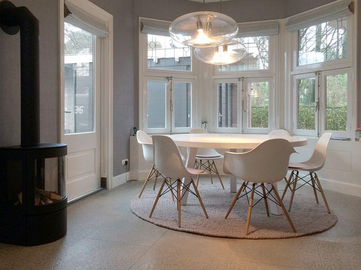 Tafel Maadi. Een ronde tafel van massief hout op maat gemaakt door Houtmerk.nl. Eromheen stoelen van Vitra, type DSW en DAW. De kussens zijn van Parkhaus en het ronde, oudroze kleed is van Perletta.