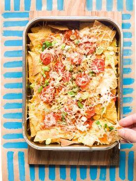 1. Halveer de kerstomaatjes en snij de pijpajuin in fijne ringetjes. 2. Giet de tortillachips in een ovenschaal. Schep de saus erover en verdeel de tomaatjes en uiringetjes erover. 3. Bestrooi met gratinkaas en kruid met chilivlokken. 4. Laat de kaas smelten onder een hete grill en serveer.