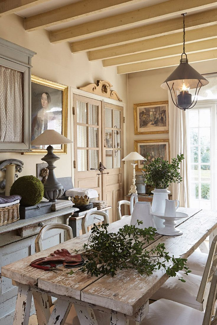Soft hues create restful harmony throughout the kitchen in this charming cottage just outside of Paris, France.