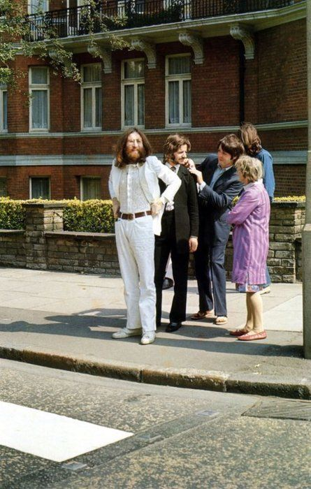 John Lennon, Ringo Starr, Paul McCartney, and George Harrison preparing to cross Abbey Road for their legendary album cover.